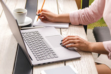 Closeup Hands Of Business Woman In Pastel Pink Shirt Working On Laptop And Making Notices In Her Notebook On Wooden Table With A Cup Of Coffee