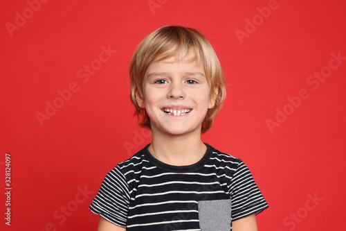 Fototapeta Portrait of happy little boy on red background obraz