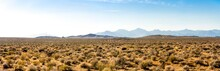 Panoramic Picture Of Death Valley With Panamit Mountain Range On A Sunny Day With Blue Sky