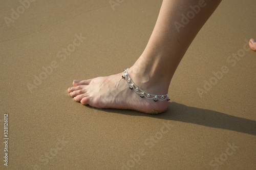 Photo Closeup of a woman's legs with an anklet jewelry on the beach