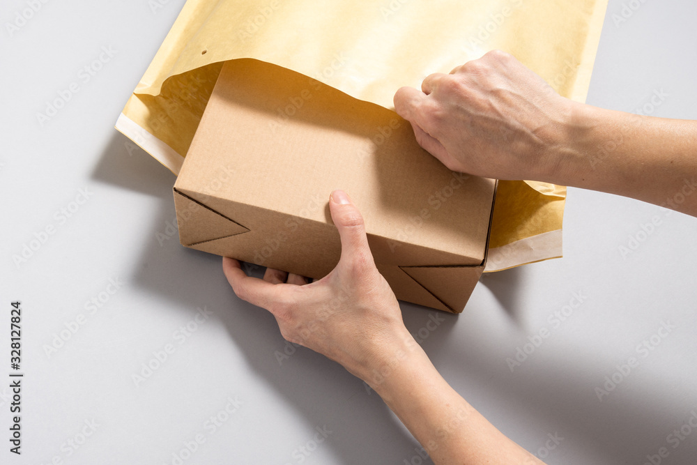 Fototapeta Woman hands puting  cardboard box inside of large postal envelope