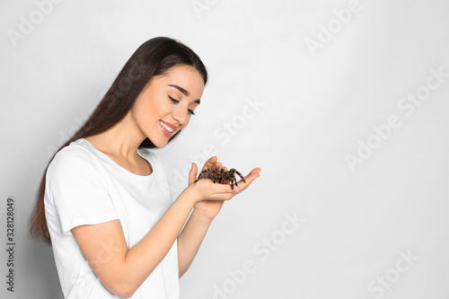 Woman holding striped knee tarantula on light background, space for text Wallpaper Mural