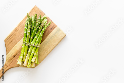 Fototapeta Cooking asparagus. Bunch steams on cutting board on white background top-down copy space obraz
