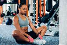 Woman Stretching Legs In Gym