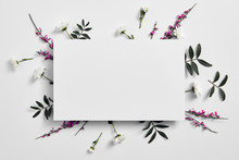 Spring Minimal Concept. Creative Flowers Flat Lay. White Paper Blank. Top View