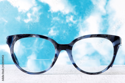 Eyeglasses Glasses with Bifocals and Black Blue Frame smudged agaist a blue and Canvas Print