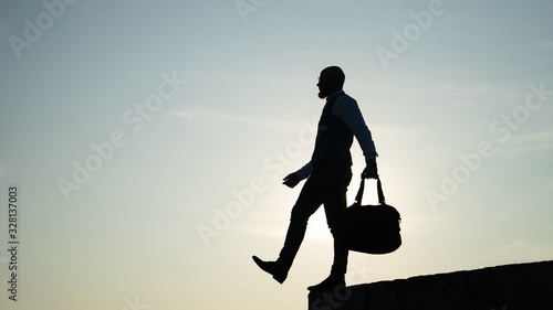 Man stepping from the edge during sunset on the sky background Wallpaper Mural