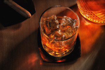 Whiskey and DGlass of Whiskey on the rocks with a cigar and decanter with strong warm sidelight.ecanter and Cigar