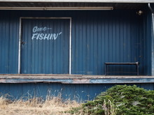 An Abandoned Blue Building With The Text, Gone Fishin'