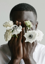 Portrait Of Handsome African Guy Who's Covering His Face With His Arms And Flowers Through His Fingers