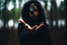 Man With Hood On With Green Watch In The Air Levitating Above His Hand In The Middle Of The A Dark Moody Forest