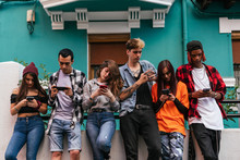 Friends Using Smartphones While Standing Outdoors