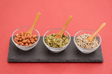 Bowls With Almonds And Pumpkin Seed, Sunflower And Wooden Spoons.