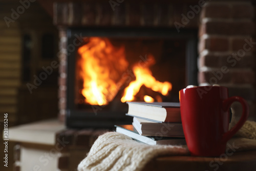 Obraz Books and cocoa on table near burning fireplace, space for text. Reading at home - fototapety do salonu