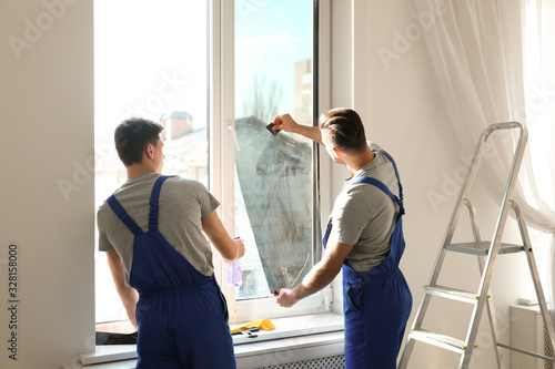 Fototapeta Professional workers tinting window with foil indoors obraz