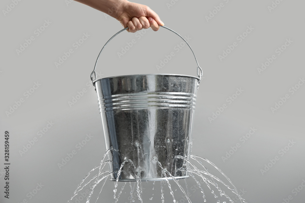Fototapeta Woman holding leaky bucket with water on light grey background, closeup