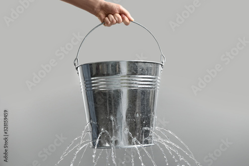 Fotomural Woman holding leaky bucket with water on light grey background, closeup