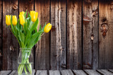 Fototapeta Tulipany - Bunch of bright yellow spring tulips in a glass container on a rustic plank table.