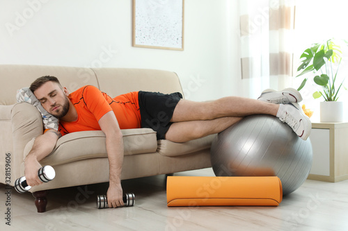 Fototapeta Lazy young man with sport equipment on sofa at home obraz