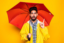 Young Handsome Bearded Indian Man In Yellow Raincoat With Red Umbrella Cover From Rain Have Idea Isolated Over Orange Background