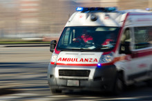 Ambulance In Italy In Emergency Driving Very Fast With Blue Lights To Accident Scene. Blurred Background.