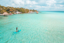 Girl Doing Paddleboard In Bacalar Lagoon, Near Cancun In Riviera Maya, Mexico
