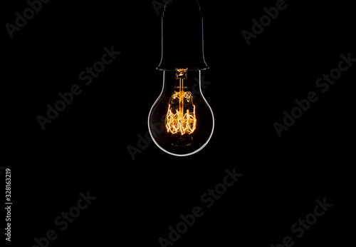 Old retro bulb isolated on a black background Canvas Print