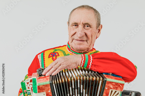 Photo A man in a national costume plays the accordion