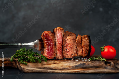 Fototapeta four steaks on  fork on a cutting board on a stone background