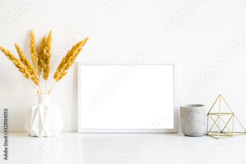 Fototapeta White frame and home decoration details on tabletop with wall, artwork poster mock-up obraz