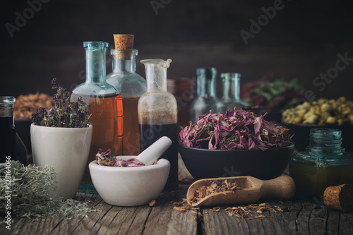 Bottles of healthy tincture or infusion, mortar and bowls of medicinal herbs on table Wallpaper Mural
