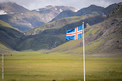 Flag of Iceland against the background of green mountains and blue sky Canvas Print