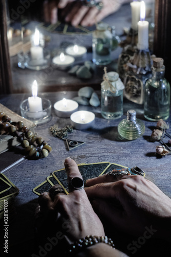 Hands of a sybil with fortunetelling cards and burning candles is reflected in a Fototapet