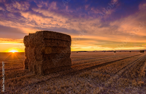 Sunset with the red sky and in the foreground a bucket of bales Fototapete