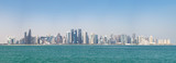 Panoramic view of modern skyline of Doha through the blue water. Concept of wealth and luxury