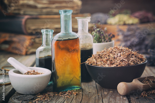 Fototapeta Healthy oak bark in bowl, infusion or tincture bottles. Mortar and bowls of medicinal herbs and books on background. Herbal medicine. obraz