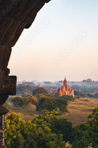 Photo Scenic view from a temple's window over Bagan's planes with ancient temples on a misty morning with warm, morning sun