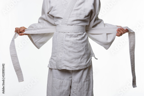Stages of correct tying of the belt by a teenager on a sports kimono, step four Wallpaper Mural