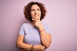 canvas print picture - Middle age beautiful curly hair woman wearing casual t-shirt over isolated pink background with hand on chin thinking about question, pensive expression. Smiling with thoughtful face. Doubt concept.