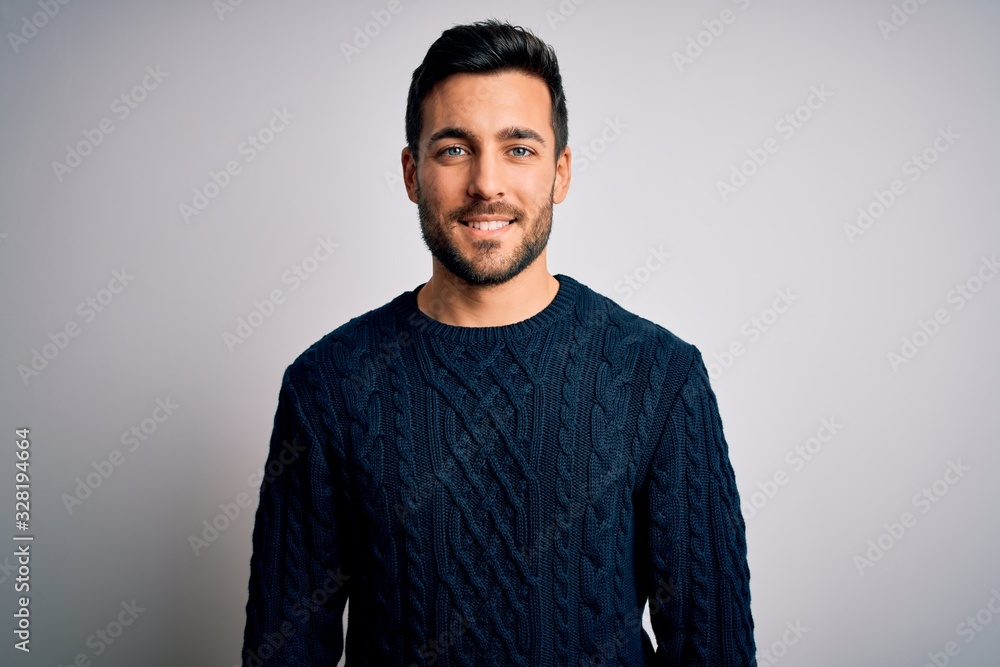 Fototapeta Young handsome man with beard wearing casual sweater standing over white background with a happy and cool smile on face. Lucky person.
