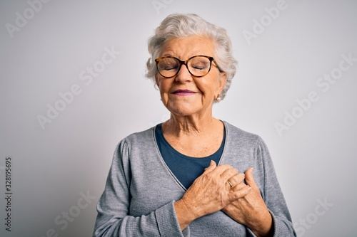 Fototapeta Senior beautiful grey-haired woman wearing casual sweater and glasses over white background smiling with hands on chest with closed eyes and grateful gesture on face