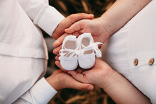Lovely Caucasian Couple Holding A Pair Of Baby Shoes While Posing Close To Each Other