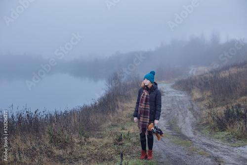 Fényképezés Sad teenager girl with  teddy bear on country road by foggy  lake