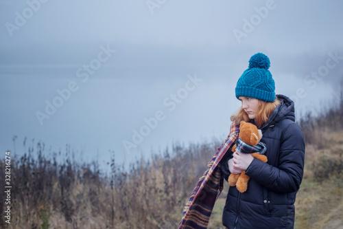 Vászonkép Sad teenager  girl hugging  teddy bear by foggy  lake