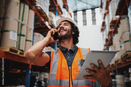 Fototapeta Low angle view of cheerful warehouse supervisor using phone for communication holding digital tablet wearing hardhat and safety vest obraz