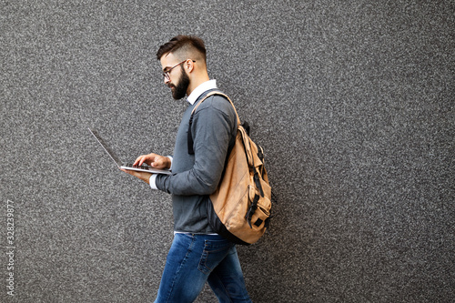 Handsome confident man using laptop computer outdoor