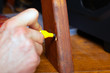 restoration and repair of wooden furniture the master hand closes the scratch with a special marker close-up