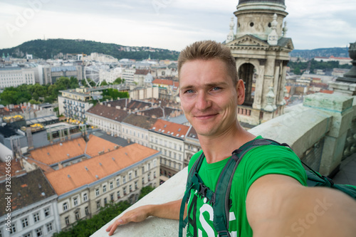 young attractive guy with blue eyes taking selfie on the top view point with Bud Canvas Print