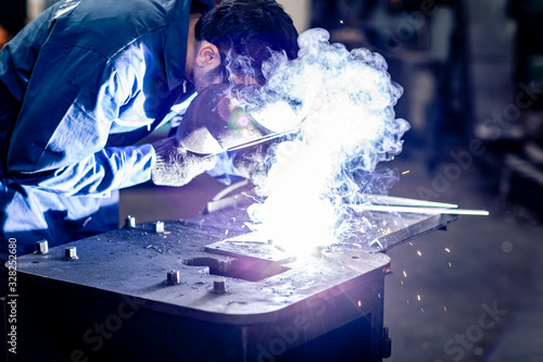 Photo worker welding metal working in steel heavy industry manufacturing