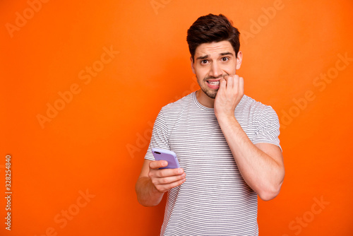 Fotomural Photo of terrified frightened millennial guy hold telephone hand biting fingers